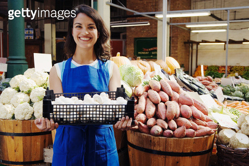 Female greengrocer holding box of mushrooms at market stall, portrait - gettyimageskorea