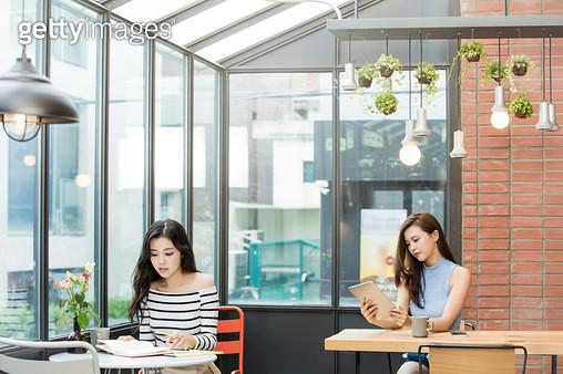 카페에서 각자 일하는 두 여성 - gettyimageskorea