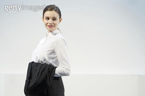 정장 자켓을 팔에 걸고 서있는 비즈니스우먼 - gettyimageskorea