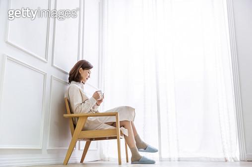 의자에 앉아 생각에 잠김 여성 - gettyimageskorea