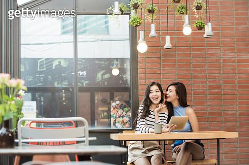 카페에서 같이 이야기하는 두 여성 - gettyimageskorea