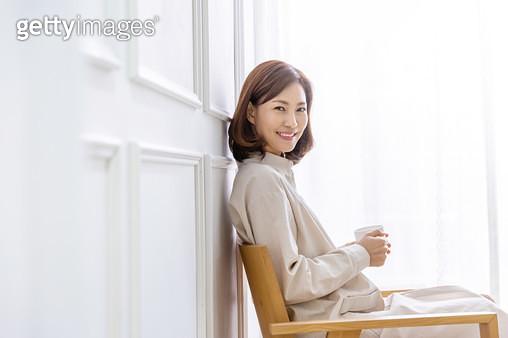 의자에 앉아 컵을 들고 환하게 웃는 여성 - gettyimageskorea