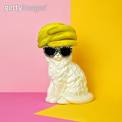White cat figurine wearing sunglasses with multiple googly eyes and a stack of bananas on its head like a yellow toupe on a pink and yellow color blocked background. - gettyimageskorea