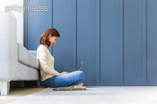 쇼파 앞에 앉아 노트북을 하는 여성 - gettyimageskorea