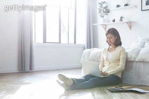 침대 앞에 앉아 노트북을 하는 여성 - gettyimageskorea