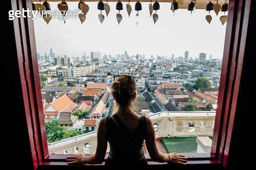 Young woman explores city, looks out from overview - gettyimageskorea