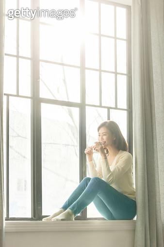 창틀에 앉아 창밖을 바라보는 여성 - gettyimageskorea