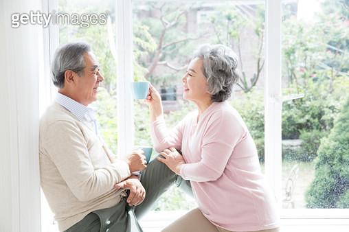창가에 앉아 대화하는 노인 부부 - gettyimageskorea