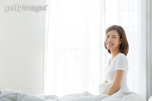 침대에 앉아 환하게 웃으며 카메라를 응시하는 여성 - gettyimageskorea