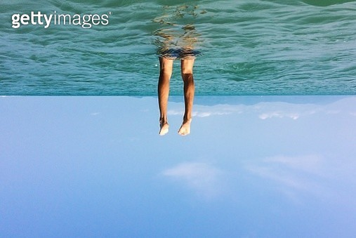 Tilt Image Of Man Swimming In Sea Against Sky - gettyimageskorea