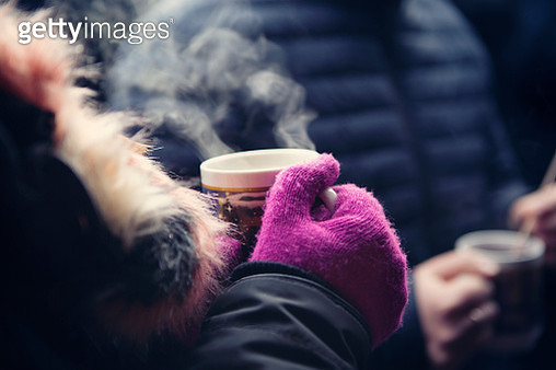 Close up of adult holding a mug of hot glühwein at a German Christmas market - gettyimageskorea