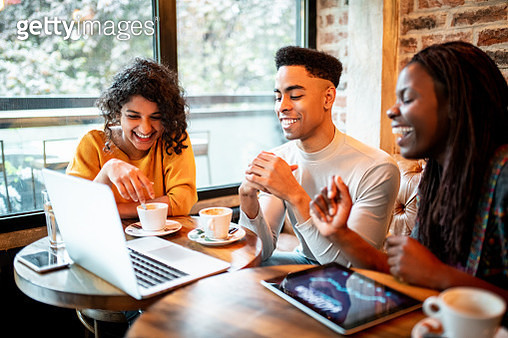 Group of smiling millennials working from the bar - gettyimageskorea
