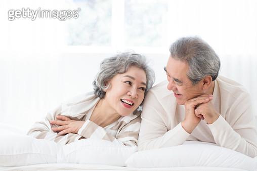 침대에 누워 속삭이며 웃는 노인 부부 - gettyimageskorea