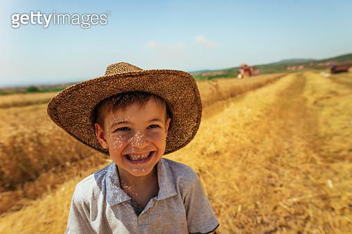 Little smiling farmer in a wheat field - gettyimageskorea