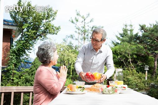 야외 테이블에서 식사하는 노인 부부 - gettyimageskorea