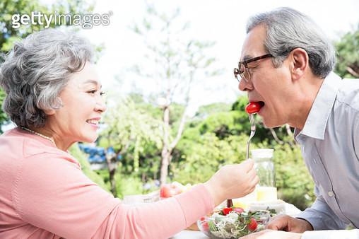 야외 테이블에서 함께 식사하는 노인 부부 - gettyimageskorea