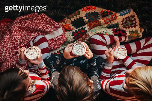 Three children sitting on a couch drinking hot chocolate - gettyimageskorea