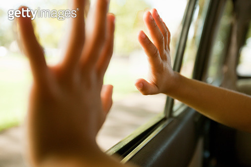 Child's hands touching car window - gettyimageskorea