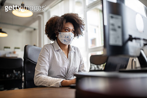 Businesswoman with face mask working at her desk - gettyimageskorea