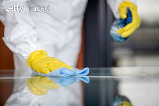 Covid-19 Wiping down surfaces. Woman with gloves and disinfectant wipe sanitizing the desk to prevent germs and bacteria infections - gettyimageskorea
