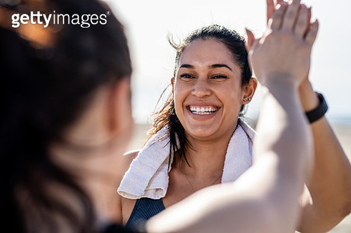 Smiling woman giving high five to her friend after exercising - gettyimageskorea