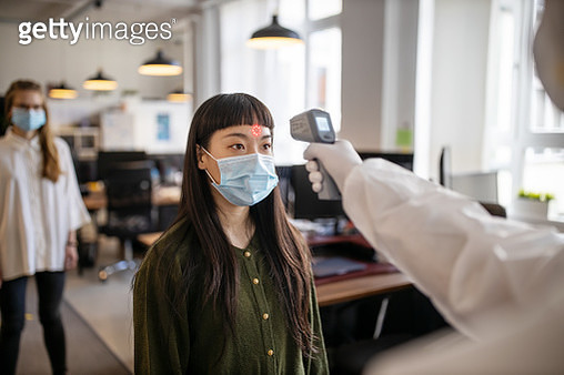 Employees going through mandatory temperature checks in office - gettyimageskorea