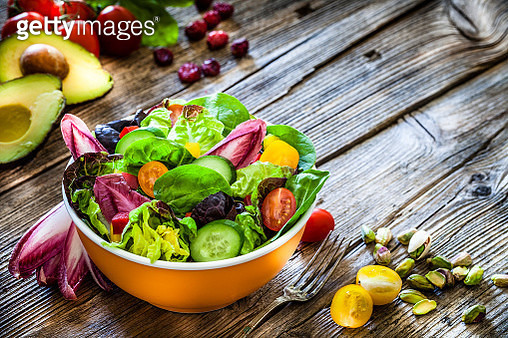 High angle view of a healthy multi colored salad bowl shot on rustic wooden table. The ingredients included for the preparation are various types of lettuce, spinach, cherry tomato, arugula and cucumber. The composition is at the left of an horizontal fra - gettyimageskorea