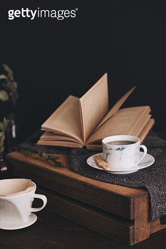 Close-Up Of Coffee Cup With Book On Table Against Black Background - gettyimageskorea