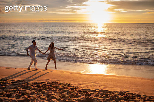 Happy young couple running on beach - gettyimageskorea