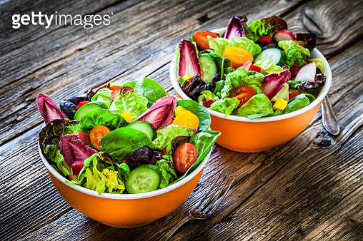 High angle view of two healthy multi colored salad bowls shot on light gray table. The ingredients included for the preparation are various types of lettuce, spinach, cherry tomato, arugula and cucumber. DSRL studio photo taken with Canon EOS 5D Mk II and - gettyimageskorea