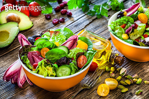 High angle view of two healthy multi colored salad bowls shot on rustic wooden table. The ingredients included for the preparation are various types of lettuce, spinach, cherry tomato, arugula and cucumber. Some vegetables for salad preparation are scatte - gettyimageskorea