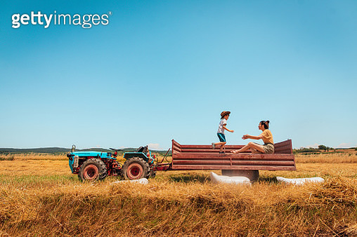 Mother and son on the tractor trailer during harvesting - gettyimageskorea