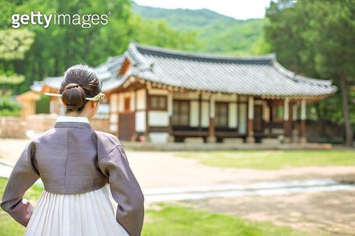 한옥 앞에 서있는 한복 입은 여자 - gettyimageskorea