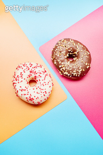 High angle view of donuts with sprinkles and chocolate on colorful background - gettyimageskorea