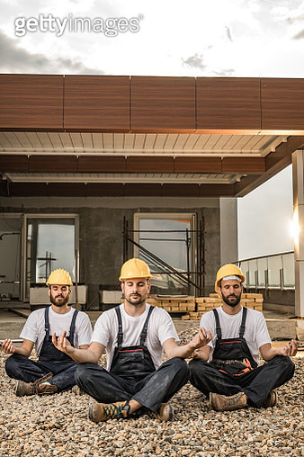 Team of workers exercising Yoga on a terrace of a construction site. - gettyimageskorea