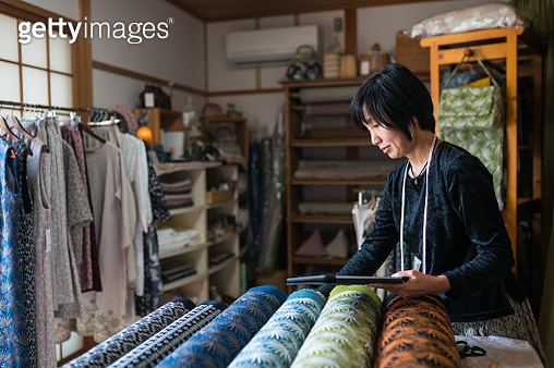 Mature woman inspecting the finished textile fabric she designed after manufacturing - gettyimageskorea