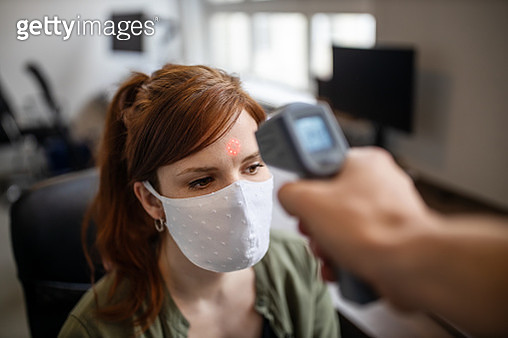 Businesswoman getting her temperature checked in office - gettyimageskorea