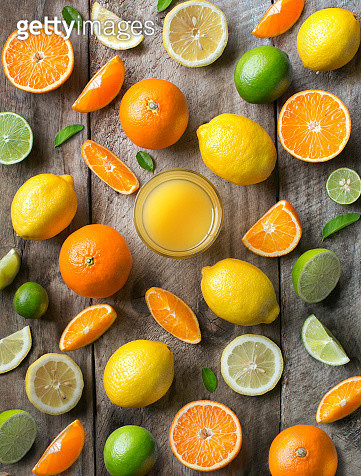 Various citrus fruits and juice in drinking glass on rustic wooden table top. - gettyimageskorea