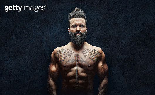 Millennial man - hippie with tattoos and beard photographed in dramatic light horizontal version. - gettyimageskorea