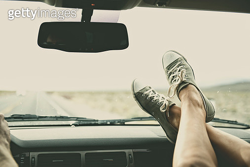 Caucasian couple riding in car with feet on dashboard - gettyimageskorea