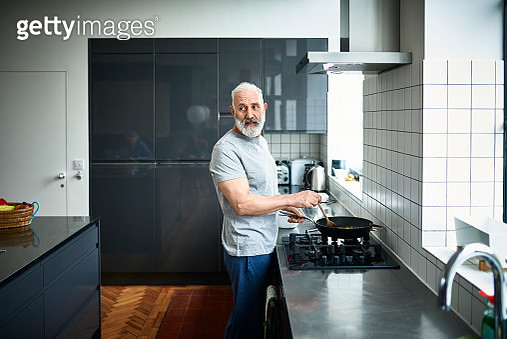 Caucasian man in his 50s looking away and preparing dinner, contemporary grey kitchen with stainless steel work surface, wearing t shirt and jeans - gettyimageskorea