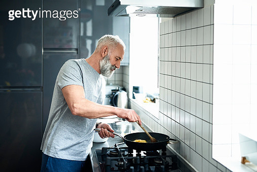 Side view portrait of man in his 50s cooking dinner, standing by stove and cooking on a gas hob, white tiled wall with natural light - gettyimageskorea