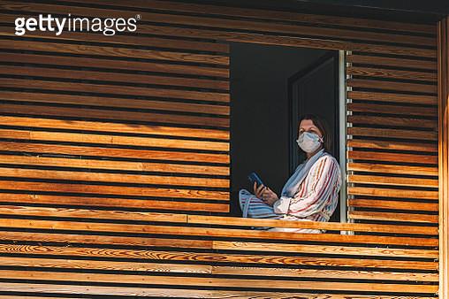 Woman in mask sitting in window of modern house - gettyimageskorea