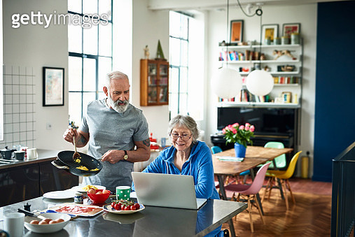 Retired couple in modern kitchen on the weekend, woman surfing the web, man holding frying pan and serving scrambled eggs - gettyimageskorea