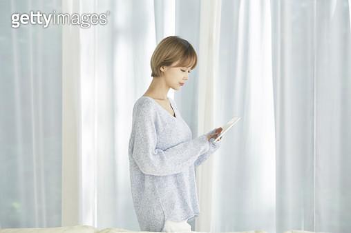 거실에 서서 태블릿pc를 보는 젊은여자 - gettyimageskorea