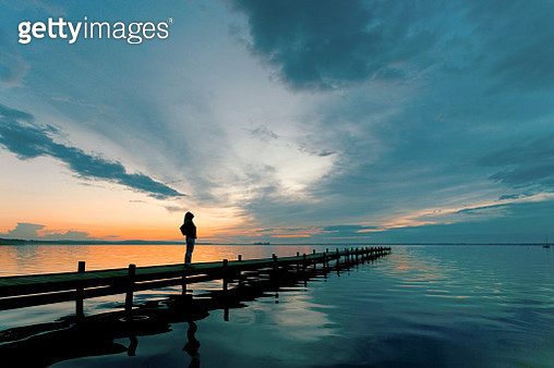 Young woman standing lakeside on jetty having a look at magical cloudscape and sunset colors.  - gettyimageskorea