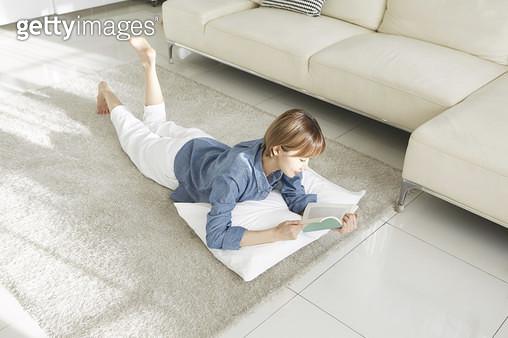 거실 바닥에 엎드려서 책을 보는 젊은여자 - gettyimageskorea