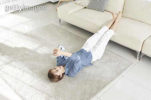 거실 바닥에 누워 소파에 다리르 올리고 휴대폰을 들고 보는 젊은여자 - gettyimageskorea