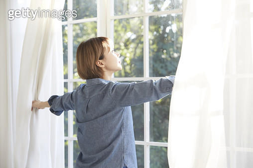 거실창 앞에 서서 커튼을 여는 젊은여자 - gettyimageskorea