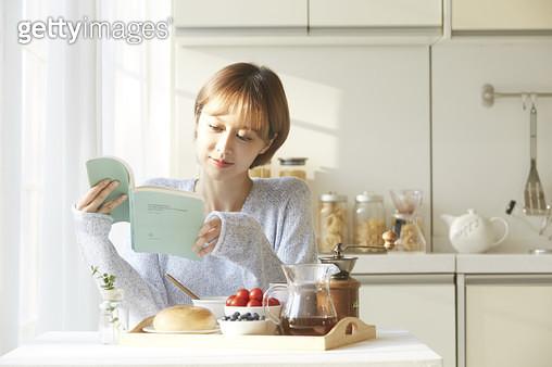 음식을 차려놓은 식탁에 앉아 책을 읽은 젊은여자 - gettyimageskorea